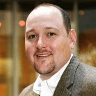 Headshot of Trent Nichols wearing a brown blazer and white collared shirt